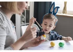 特写母亲向小男孩展示如何画鸡蛋_6986895