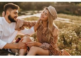 男人和女人坐在草地上轻轻地互相抚摸浪漫_12432401