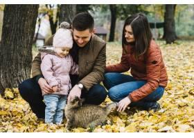 秋天公园里年轻的父母和小孩子在玩猫_2816551