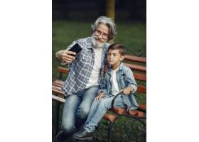 男孩和爷爷坐在长凳上一家人在公园里老_10063067