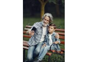男孩和爷爷坐在长凳上一家人在公园里老_10063072
