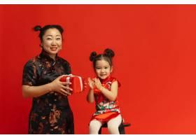 穿着传统服装孤立在红色墙上的亚洲母女肖像_13058656