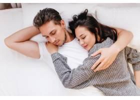 穿着白色T恤的疲惫男子在妻子睡觉时拥抱她_10786164