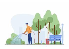 一名男子在城市公园里穿着软管浇水灌木丛_10613203
