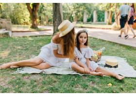 高兴的黑发女孩坐在母亲身边的毯子上抚摸_10484583