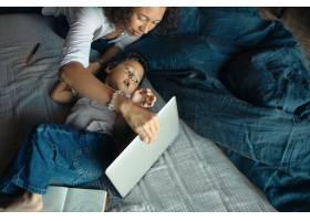 高空拍摄严肃的年轻黑皮肤女子在卧室里使用_11554413