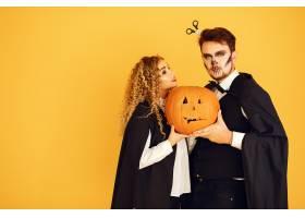 黄色背景上的情侣穿着黑色戏服的女人万_10706832