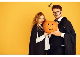 黄色背景上的情侣穿着黑色戏服的女人万_10706834