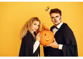 黄色背景上的情侣穿着黑色戏服的女人万_10706836