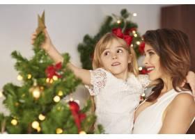 母亲在圣诞树顶上的女儿_11777900