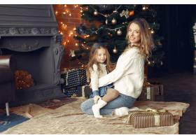 母亲带着可爱的女儿在家中靠近壁炉的地方_11241884