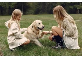 母亲和女儿在玩狗秋天公园的一家人宠物_11191026