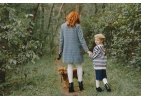 母亲和女儿在玩狗秋天公园的一家人宠物_11193197