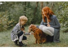 母亲和女儿在玩狗秋天公园的一家人宠物_11193205