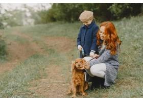 母亲和女儿在玩狗秋天公园的一家人宠物_11193285