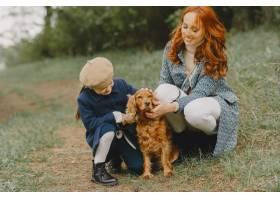 母亲和女儿在玩狗秋天公园的一家人宠物_11193292
