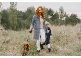 母亲和女儿在玩狗秋天公园的一家人宠物_11193304