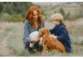 母亲和女儿在玩狗秋天公园的一家人宠物_11193357