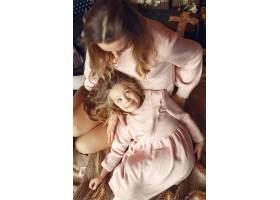 母亲带着可爱的女儿在家中靠近壁炉的地方_11241954