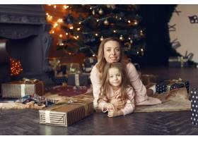 母亲带着可爱的女儿在家中靠近壁炉的地方_11241960