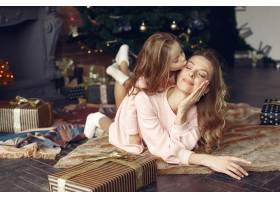 母亲带着可爱的女儿在家中靠近壁炉的地方_11241973