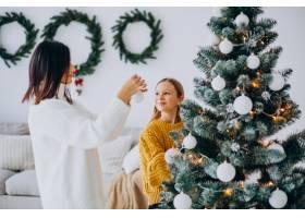 母亲带着女儿装饰圣诞树_12177325