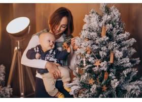 母亲带着她的男婴庆祝圣诞节_11981332