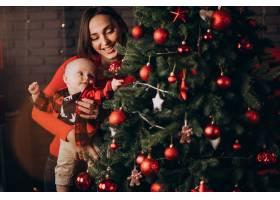 母亲带着她的男婴庆祝圣诞节_11981353