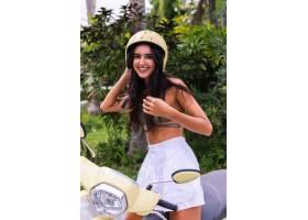 快乐晒黑的女人在户外戴着头盔骑摩托车_11305297