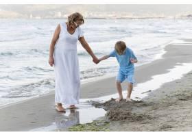 祖母和男孩在海滩上散步_10849877