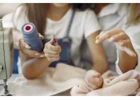 母亲带着年幼的女儿在工厂缝制衣服_6632295