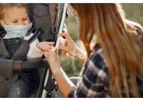 母亲戴着口罩大流行期间母亲抱着婴儿车_11160472