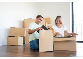 积极的夫妇在新公寓里打开东西坐在地板上_11076319