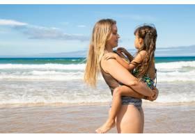 积极的年轻母亲抱着小女儿抱着孩子站在_11076346
