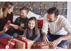 快乐的孩子和父母一起打开圣诞礼物_11757022