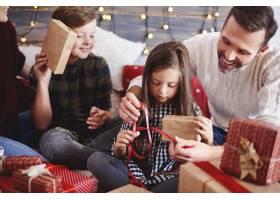快乐的孩子和父母一起打开圣诞礼物_11757083