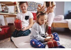 快乐的兄弟姐妹打开圣诞礼物_11756953