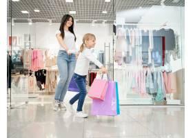 快乐的女孩和妈妈走在现代百货公司_8792610