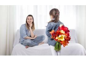 母亲节手持鲜花的小女儿祝贺她的母亲_10922902
