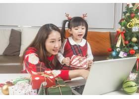 快乐的妈妈和小女儿在家里装饰圣诞树和礼物_11548030