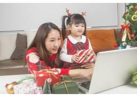 快乐的妈妈和小女儿在家里装饰圣诞树和礼物_11548032