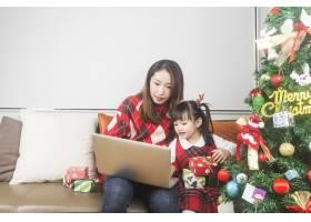 快乐的妈妈和小女儿在家里装饰圣诞树和礼物_11548033