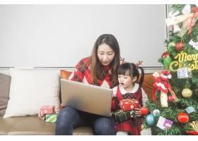 快乐的妈妈和小女儿在家里装饰圣诞树和礼物_11548035