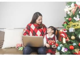 快乐的妈妈和小女儿在家里装饰圣诞树和礼物_11548036