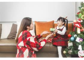 快乐的妈妈和小女儿在家里装饰圣诞树和礼物_11548038