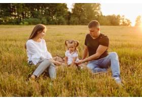 秋天田野里幸福的一家人母亲父亲和婴儿_11033744