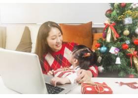快乐的妈妈和小女儿在家里装饰圣诞树和礼物_11548051
