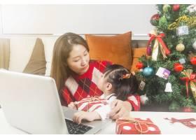 快乐的妈妈和小女儿在家里装饰圣诞树和礼物_11548055