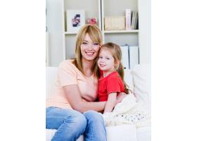 快乐的年轻母亲坐在沙发上拥抱她可爱的小女_10879578
