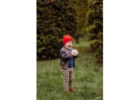 快乐的微笑着的孩子在花园里户外玩耍_11035189